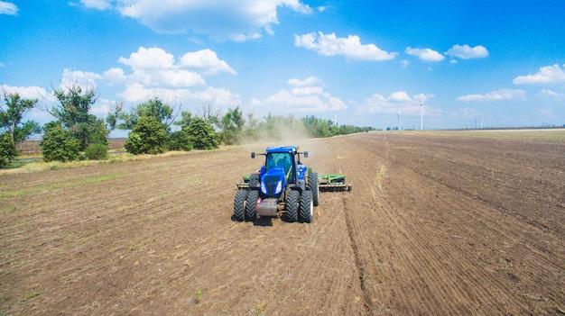 Een tractor die en in het gebied ploegt zaait
