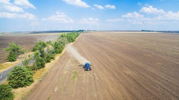 Een tractor die en op gebied ploegt zaait