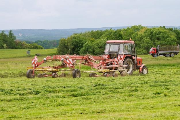 Een tractor met een cirkelhark harkt vers gemaaid gras voor kuilvoer op een groot veld.