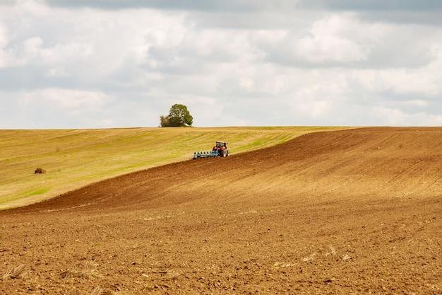 Een tractor met een grote ploeg ploegt een veld