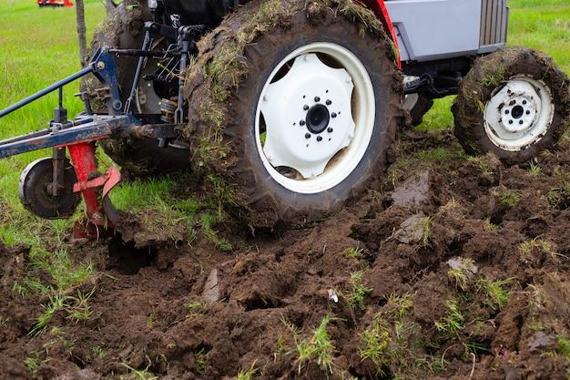 Een tractor met een ploeg ploegt in het voorjaar een landbouwveld om aardappelen te planten. het land ploegen, close-up.