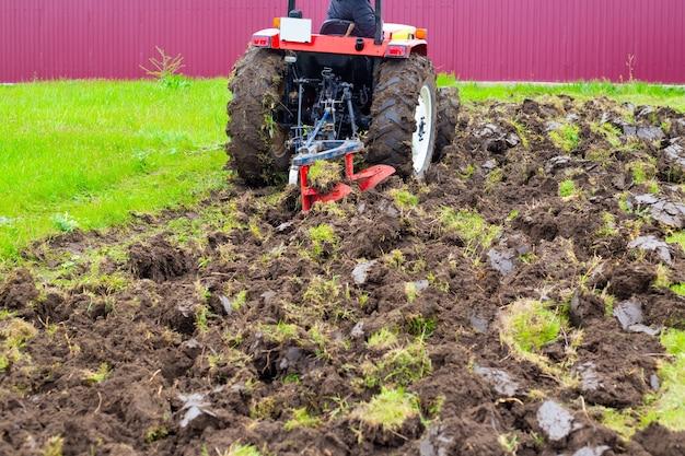 Een tractor met een ploeg ploegt in het voorjaar een landbouwveld om aardappelen te planten. het land ploegen.
