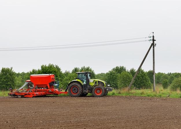 Een tractor met een zaaicomplex verwerkt landbouwgrond veld