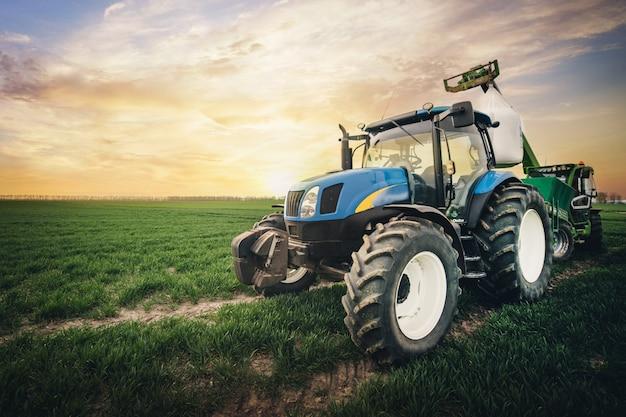 Een tractor met een zak kunstmest rijdt in het voorjaar langs het veld