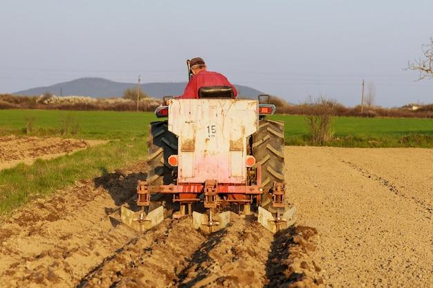 Een tractor op het veld plant aardappelen en bewerkt de grond