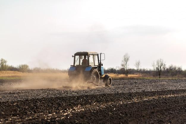 Een tractor ploegt een veld voor het zaaien van gewassen