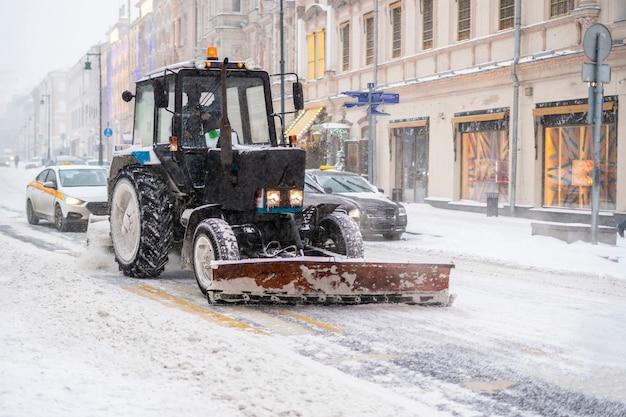 Een tractor reinigt de straat van sneeuw na een sneeuwstorm