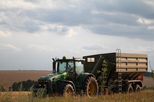 Een tractor voor het verzamelen van tarwe uit een maaidorser staat op een veld van gemaaide tarwe tegen een blauwe bewolkte hemel
