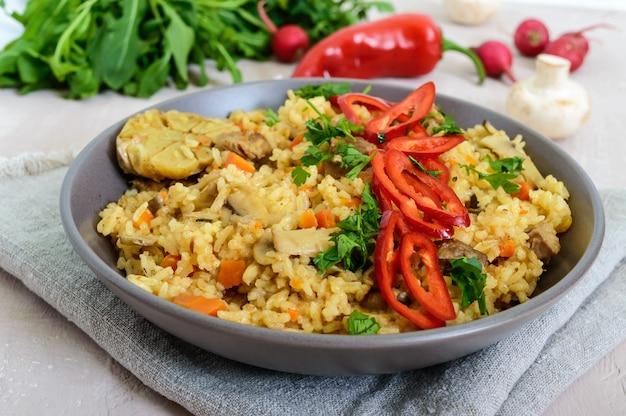 Een traditioneel aziatisch gerecht - pilaf met vlees, champignons en pepercapi in een kom