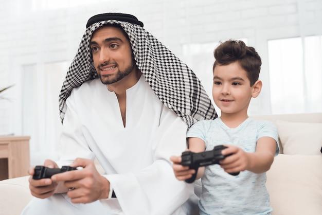 Een traditionele arabische familie speelt een gameconsole.
