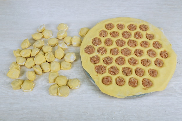 Een traditionele slavische nationale voedsel rauwe dumplings op een ronde plank, bovenaanzicht tijdens het koken van dumplings van meel en vlees