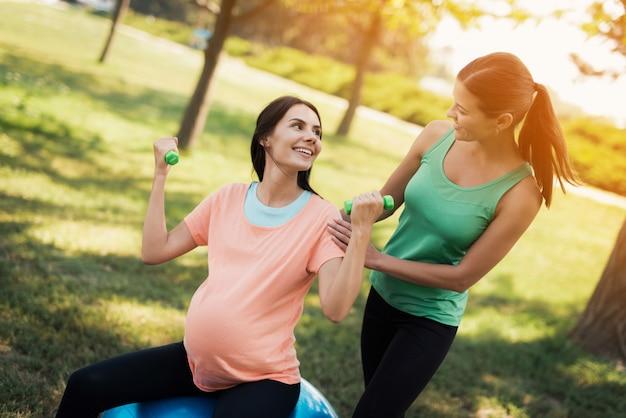 Een trainer in een groene trui helpt een zwangere vrouw in een roze