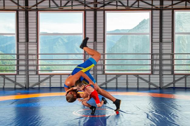 Een trainer in sportworstelkousen leert een kleine worstelaarsjongen