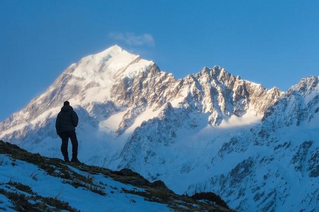 Een tramper staande op een heuvel in hooker valley onder de zuidkant van aoraki mount cook en nazomi