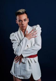 Een transgender model met lange nagels en een donkerblauwe achtergrond