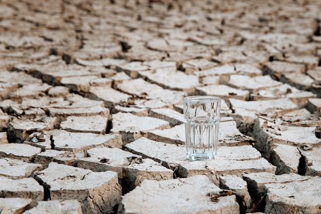 Een transparant glas schoon drinkwater staat in het midden van droog, gebarsten woestijnland, concept van opwarming van de aarde, droogte en watercrisis