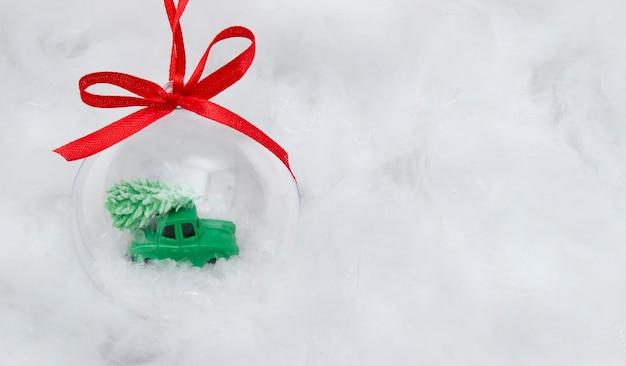 Een transparante bal met een speelgoedauto en kerstboom in de sneeuw