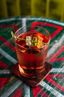 Een transparante cocktail in een longdrinkglas met een groot ijsblokje gegarneerd met gummibeertjes