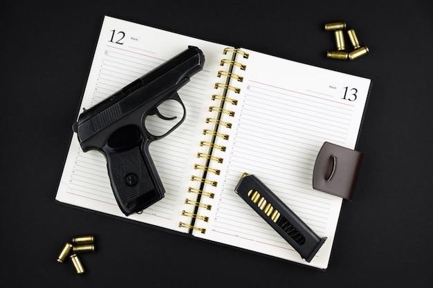 Een traumatisch pistool en munitie liggen op een geopend notitieboekje op een zwarte ondergrond