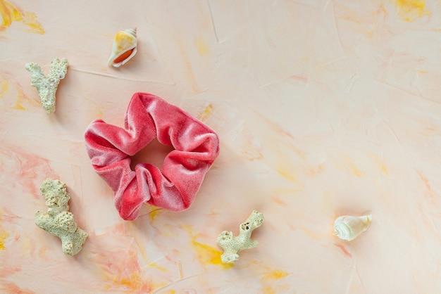 Een trendy fluwelen scrunchie, zeeschelpen en koralen op roze achtergrond. plat lag, bovenaanzicht. diy-accessoires, kapsels, levensstijl, zeevakantie en planningsconcept voor de zomervakantie, kopieerruimte