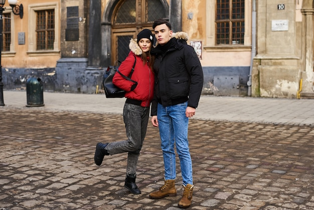 Een trendy jong paar loopt in de stad bij christmastime