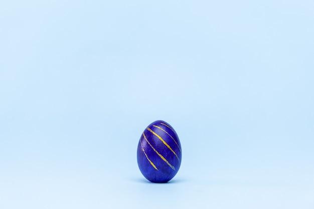 Een trendy paasei gekleurd klassiek blauw, wit en goudkleurig op blauw