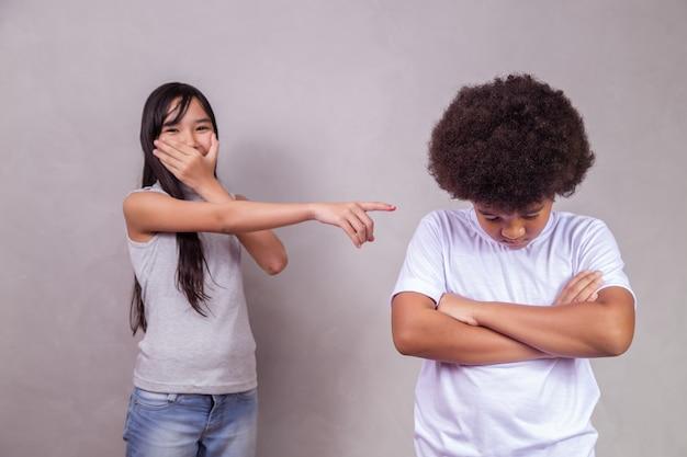 Een triest moment van intimidatie van een zwarte jongen die wordt gepest. meisje lacht grapjes over de jongen