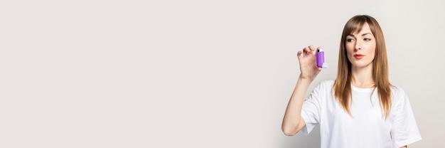 Een trieste jonge vrouw houdt een inhalator in haar hand, kijkt naar de inhalator