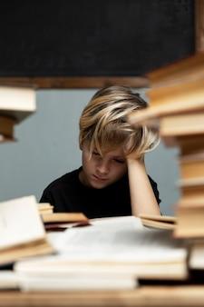 Een trieste jongen in een zwart t-shirt zit aan een tafel met een stapel boeken