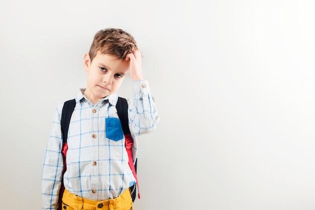 Een trieste jongen met een rugzak tegen een witte achtergrond.