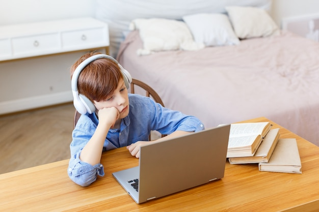 Een trieste jongensleerling met een koptelefoon voor een laptopmonitor tijdens een online les is hij saai