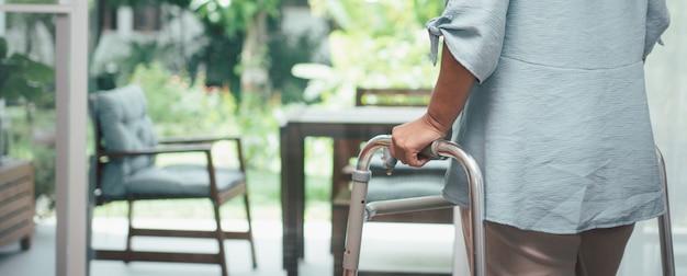 Een trieste oude oudere vrouw gebruikt walker om voor ramen te staan en naar buiten te kijken