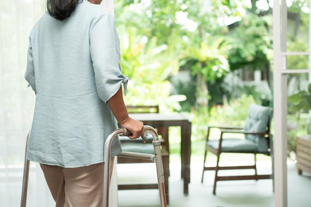 Een trieste oude oudere vrouw gebruikt walker om voor ramen te staan