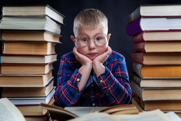 Een trieste schooljongen met bril zit aan een tafel met een stapel boeken. leer moeilijkheden. zwarte ruimte.