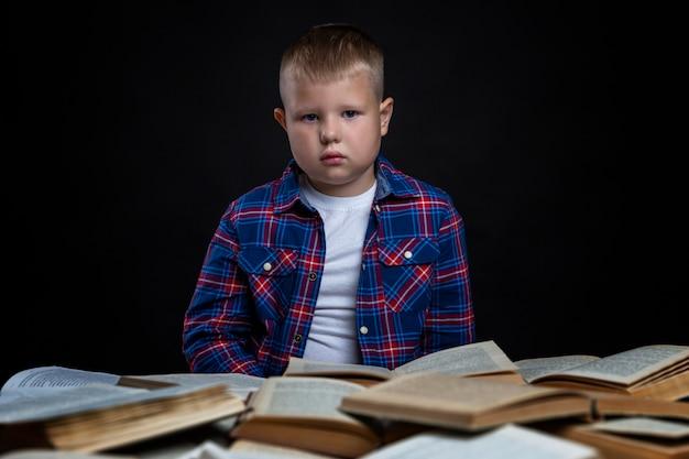 Een trieste schooljongen zit aan een tafel met open boeken. leer moeilijkheden. zwarte ruimte.