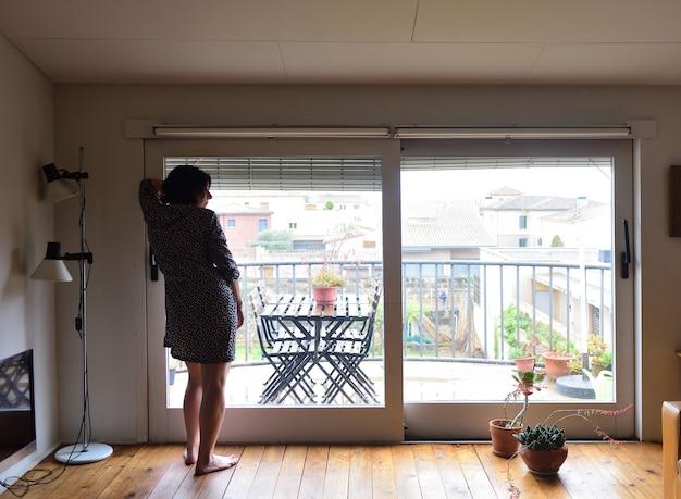 Een trieste vrouw kijkt uit het raam thuis