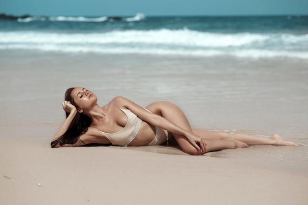 Een tropisch model met sproeten op haar gezicht en beige bikini ontspannend aan zee