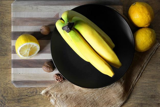 Een tros bananen en citroenen op een zwarte plaat