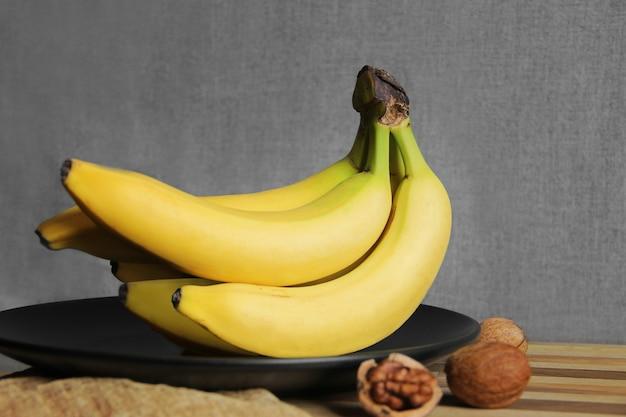 Een tros bananen op een zwarte plaat