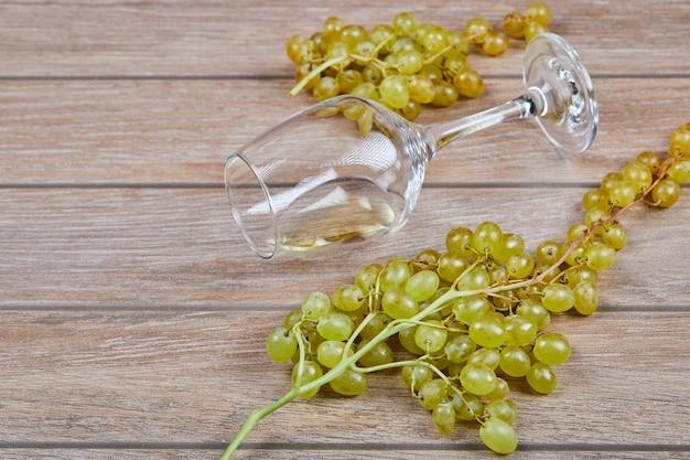 Een tros druiven en wijnglas op houten oppervlak