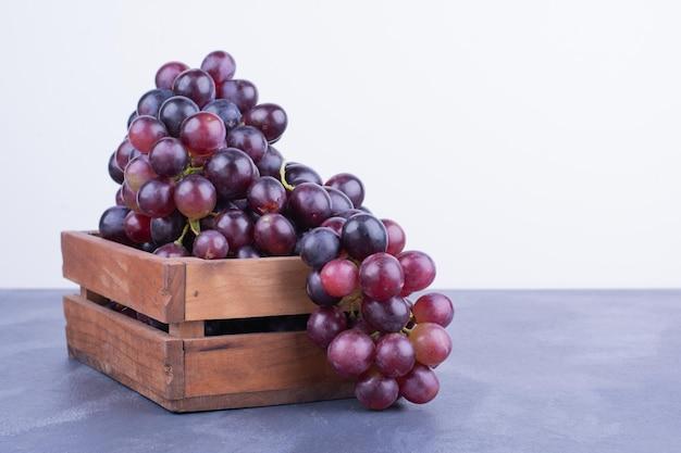 Een tros druiven in een houten dienblad.