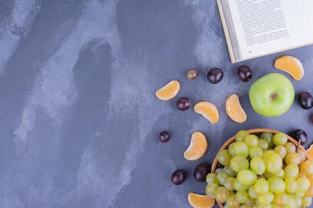 Een tros wijndruiven op een houten bord.