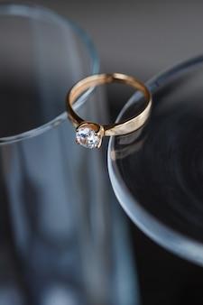 Een trouwring van edelmetaal met een diamantsteen ligt in een glas