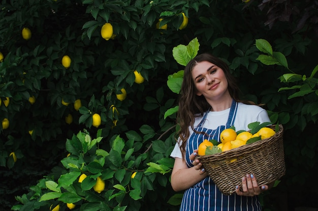 Een tuinman in een gestreept blauw schort staat in de tuin met een mand met citroenen