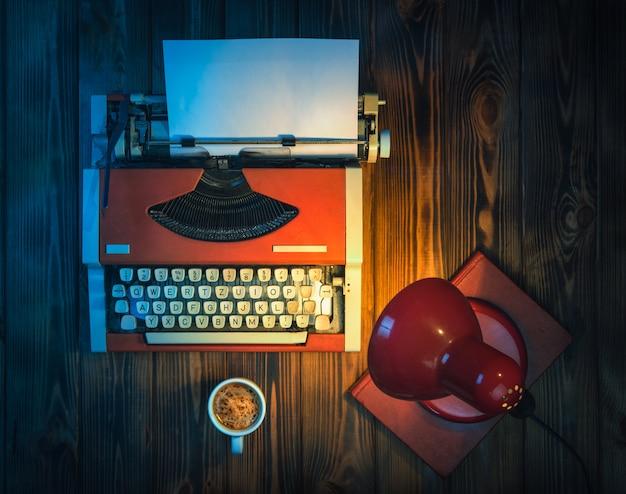 Een typemachine en koffie in het licht van een lamp.