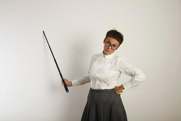 Een uitgeputte en uitgebrande lerares in ouderwetse kleding die bij een whiteboard met een wijzer staat