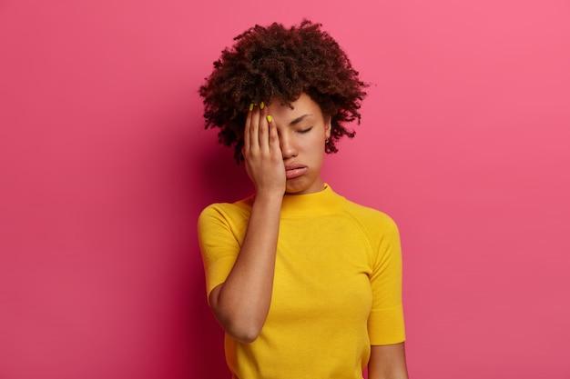 Een uitgeputte jonge vrouw met een donkere huid bedekt de helft van het gezicht, zucht van vermoeidheid, heeft een slaperige uitdrukking, sluit de ogen, draagt een geel t-shirt, poseert over een roze muur. vrouw voelt zich verveeld en moe