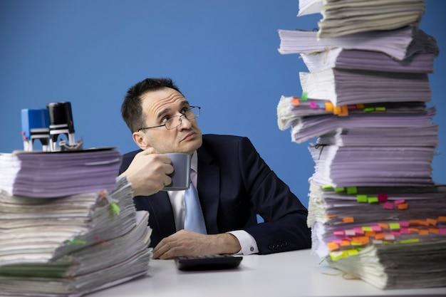 Een uitgeputte zakenman heeft te veel papierwerk en kijkt naar een hoge stapel documenten