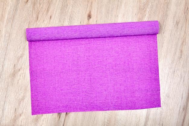 Een uitgevouwen rol lila verfrommeld papier ligt op een eikenhouten vloer.