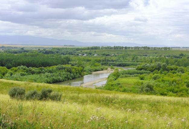 Een uitlopersvlakte begroeid met gras en bos onder een blauwe zomer bewolkte hemel. siberië, rusland